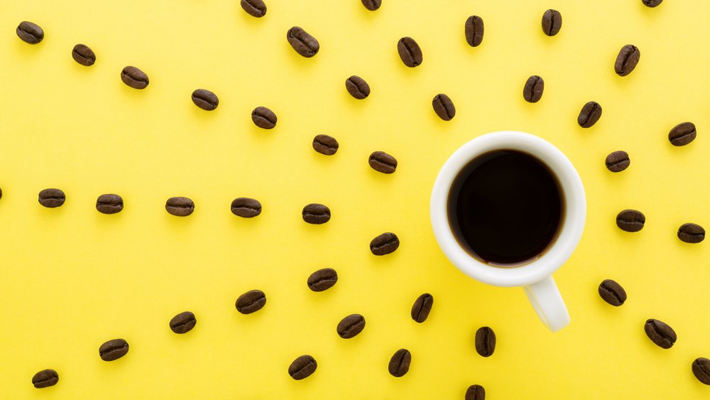 cup of coffee with coffee beans around it on a yellow background