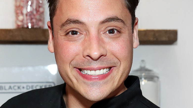 Jeff Mauro smiling in chef's jacket