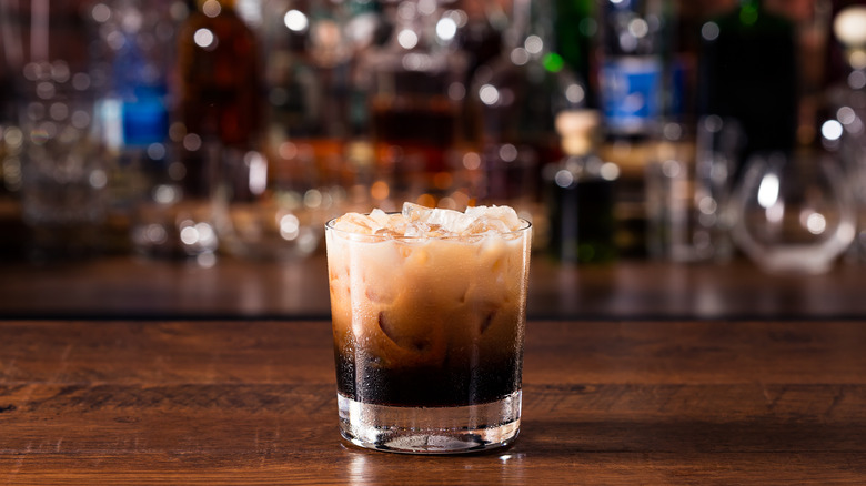 A glass with dark liqueur and cream on wood table