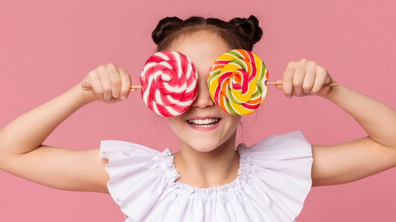 Girl holding lollipops in front of her eyes