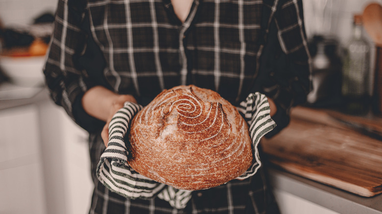 Person holding a loaf of sourdough bread