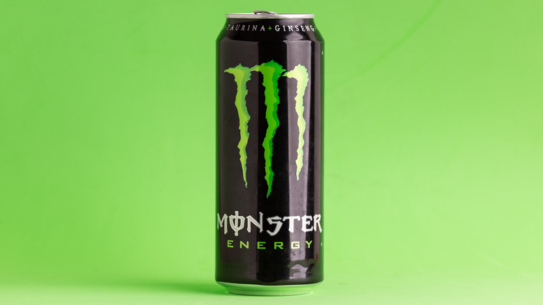 A can of Monster Energy Drink on green background