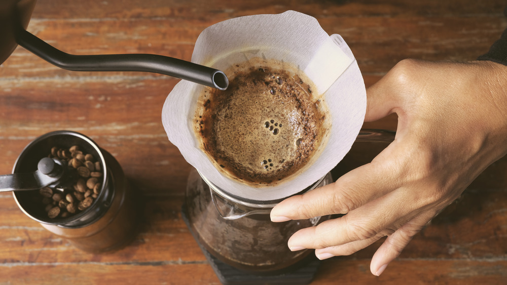 Barista pouring hot water in coffee