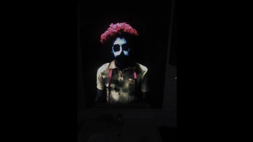 Creepy clown dressed similar to Ronald McDonald in mirror