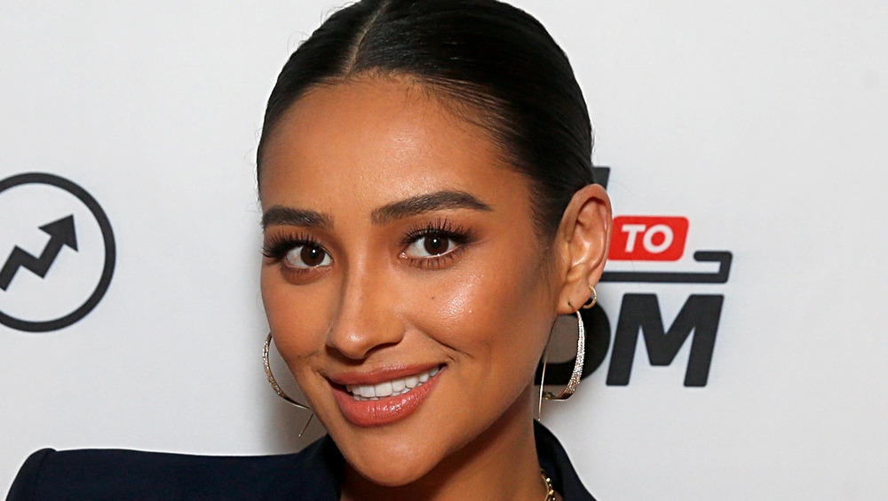 Shay Mitchell wearing gold hoops