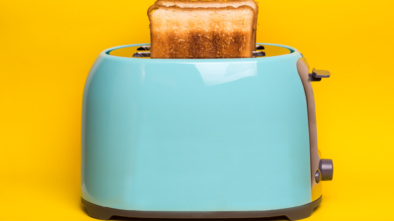 Light blue toaster with cooked pieces of toast