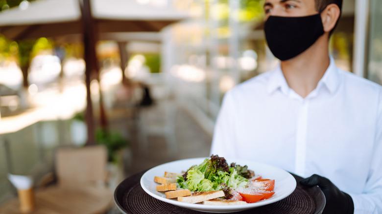 Waiter wearing a mask serving a salad
