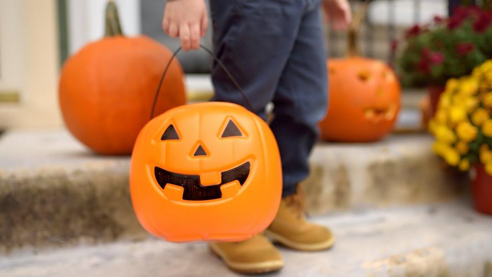 child with pumpkin-shaped halloween bucket