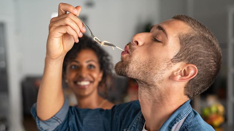Man eating pasta off a fork