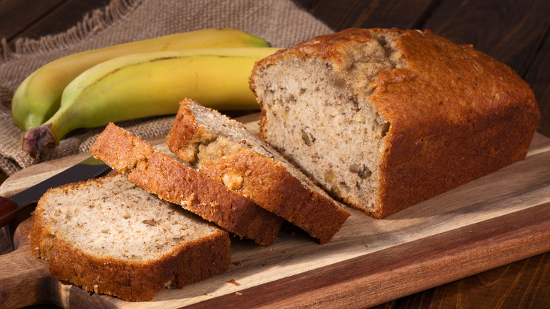 loaf of banana bread with fresh bananas next to it