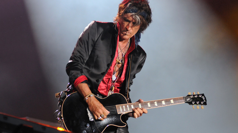 Joe Perry playing guitar on stage