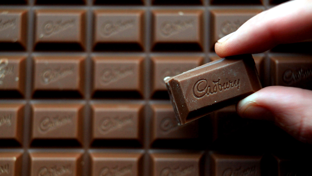 Person holding a square of Cadbury chocolate