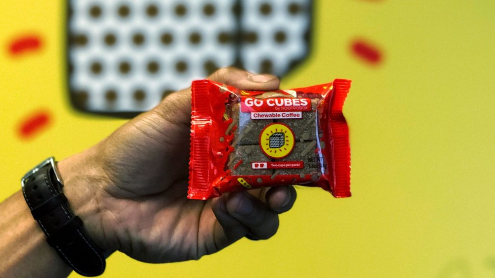 A hand holding a package of Go Cubes