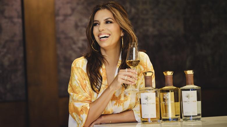Eva Longoria sips Casa Del Sol Tequila with bottles on a bar