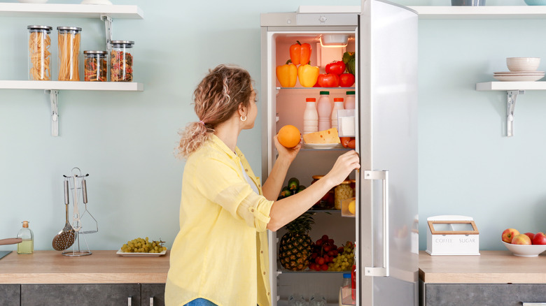 A woman taking an orange out of the fridge