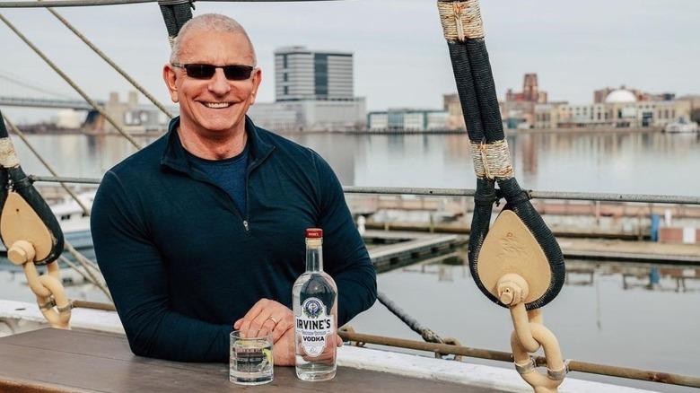 Robert Irvine smiling with vodka bottle