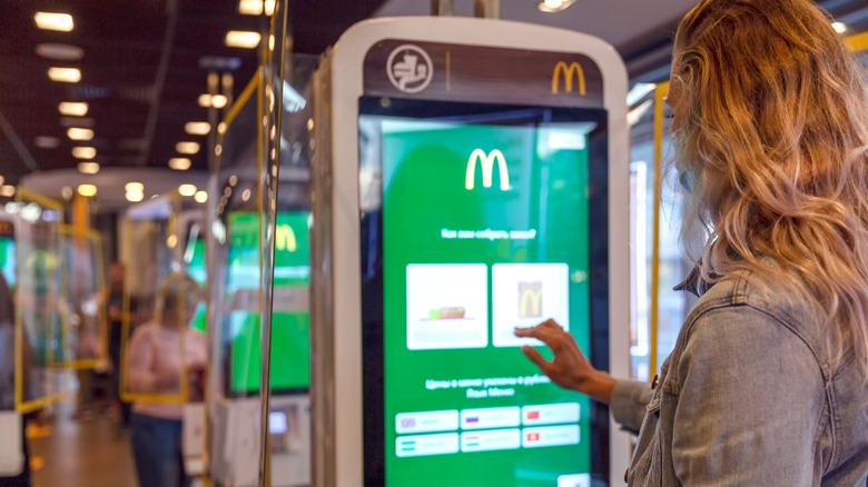 Woman using McDonald's self-serve kiosk