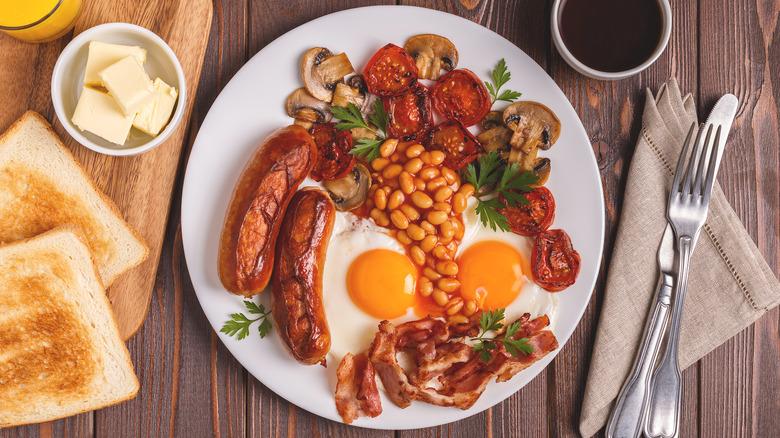 Full English breakfast platter on wood table