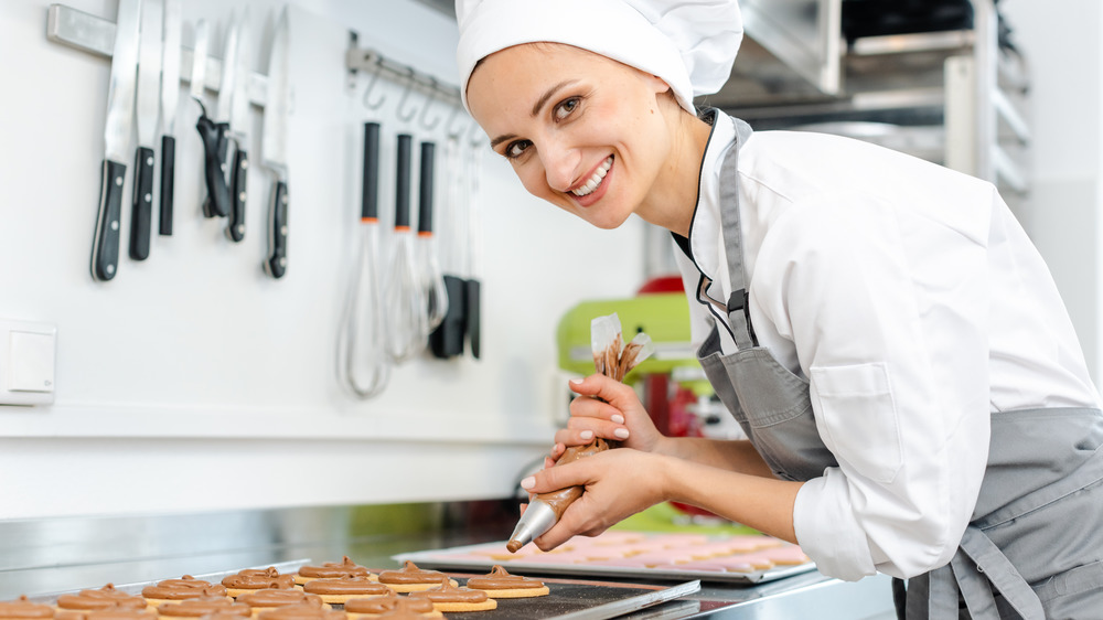 smiling chef decorating cookies