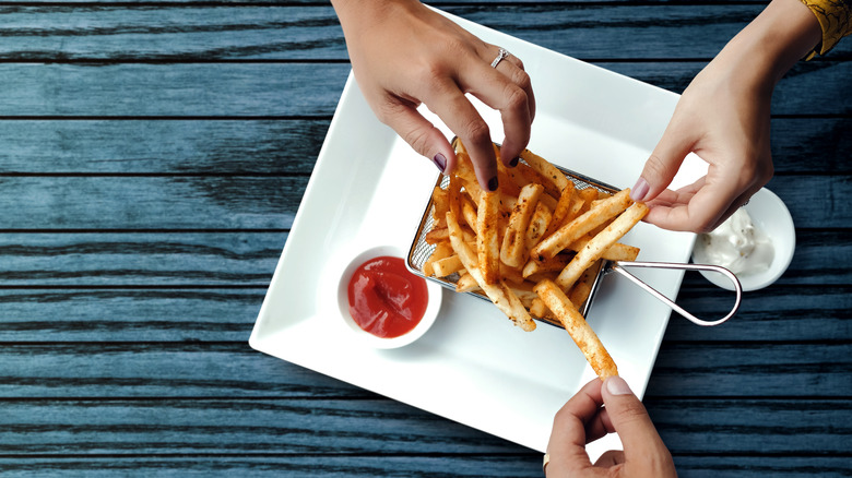 Three hands grabbing some french fries
