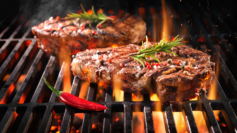 Two steaks over fire grill with pepper