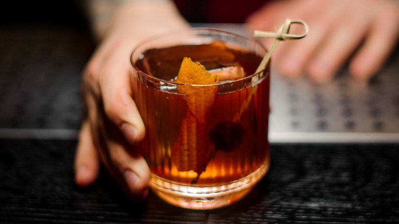 Hand holding old fashioned drink