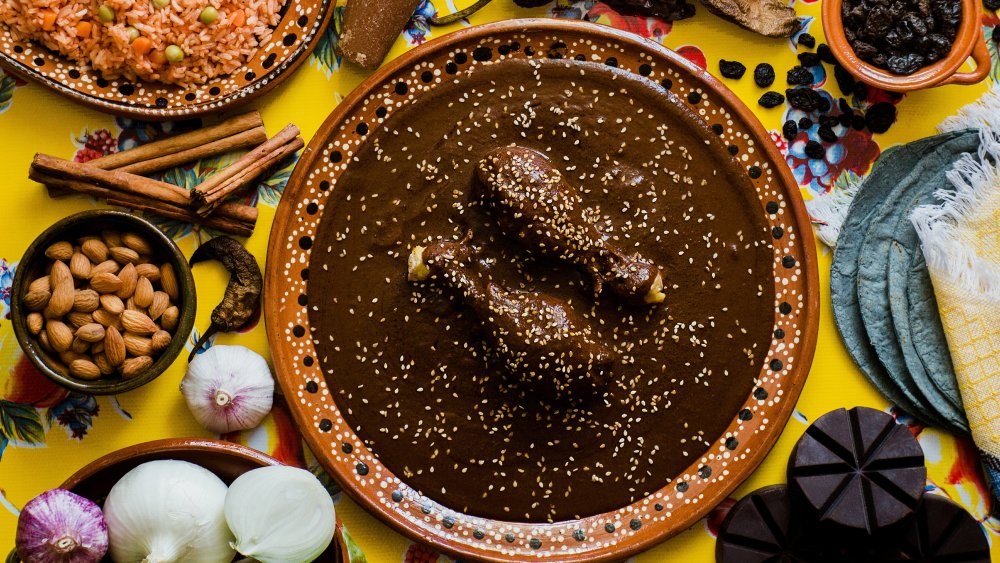 Mole sauce on chicken surrounding by dinner spread