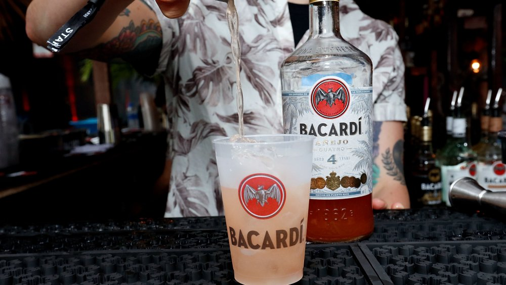 A bartender makes a drink with Bacardi