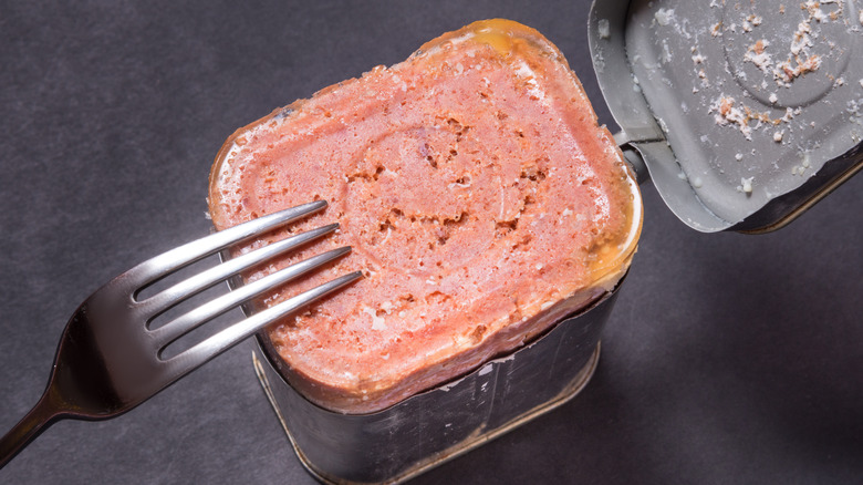 opened corned beef can with fork