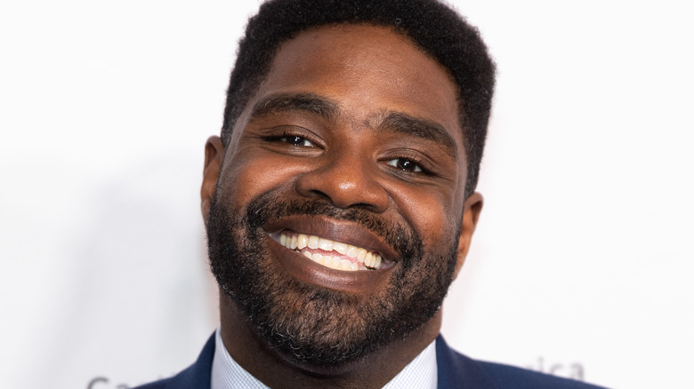Ron Funches smiling in suit