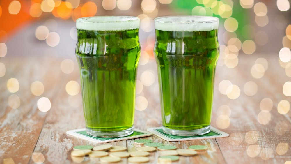 glasses of green beer with gold coins