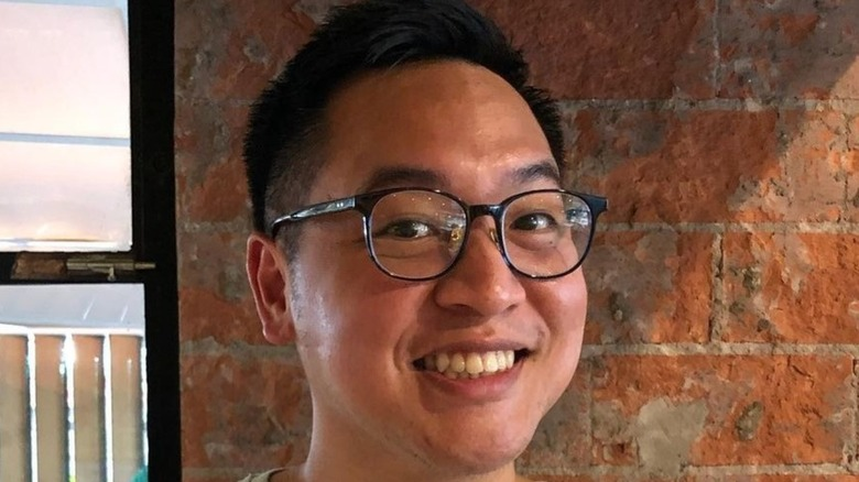 Justin Yu wearing glasses and smiling