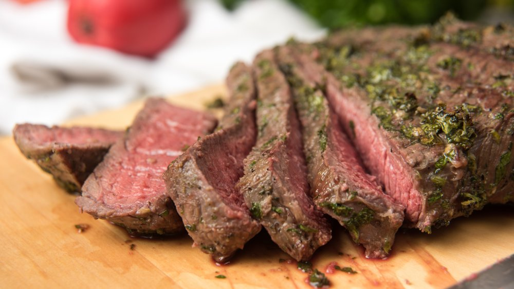 Sliced medium-rare London broil topped with herbs on cutting board.
