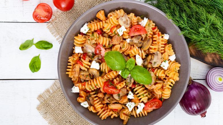radiatori pasta dish with tomatoes, herbs, mushrooms, and cheese