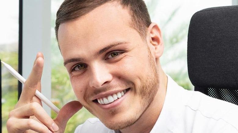 Amaury Guichon smiling and holding pen