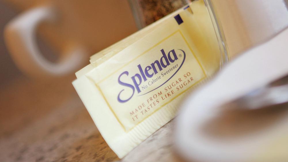Splenda packets next to a white mug
