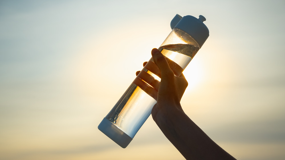 plastic water bottle with setting sun