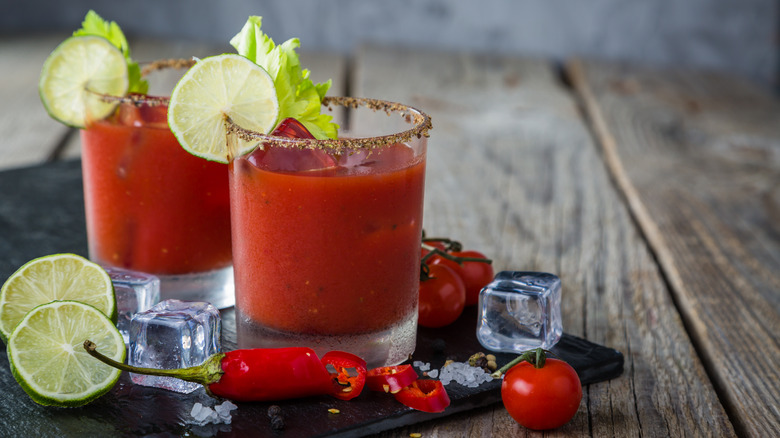 Two Bloody Mary cocktails with limes and peppers