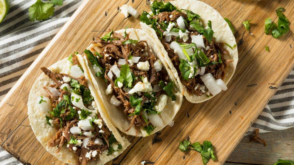 Barbacoa tacos with cilantro, lime, onion and flour tortillas