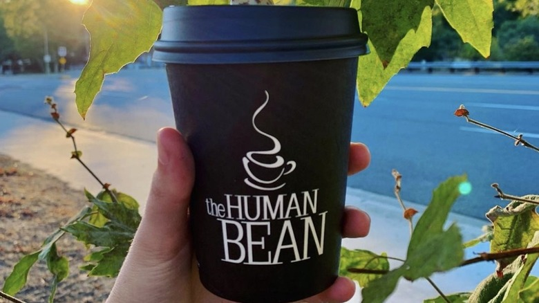 Hand holding The Human Bean coffee cup