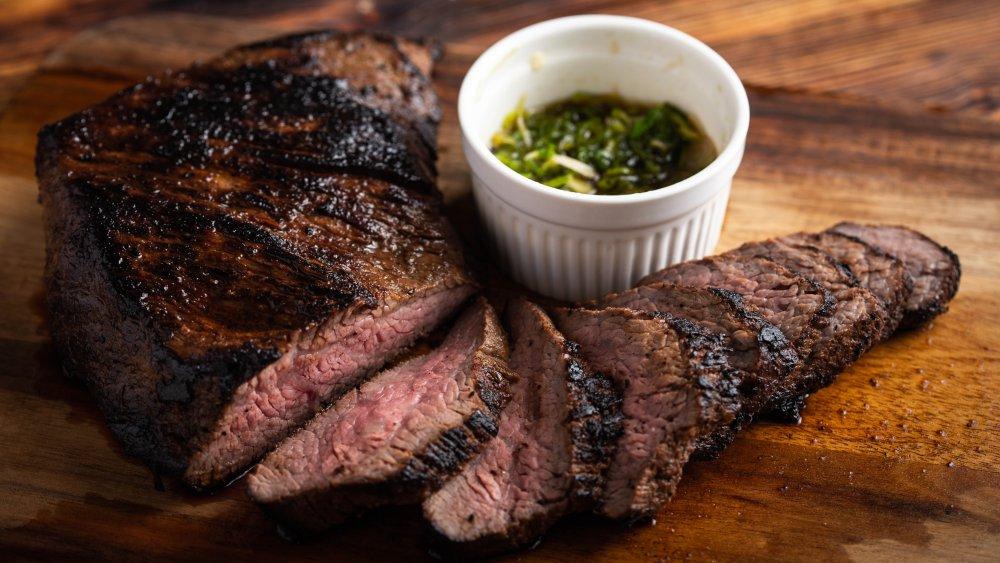 grilled tri-tip steak on wood background