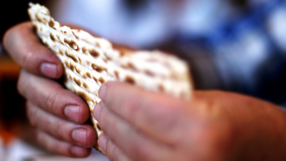 Two hands holding unleavened bread.