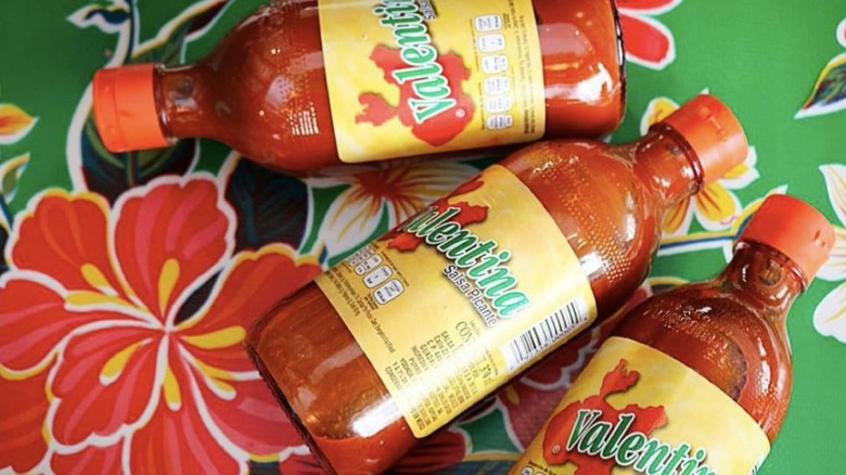 Bottles of Valentina hot sauce on floral background