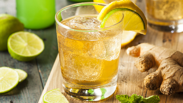 Glass of ginger ale with pieces of ginger and a slice of lime