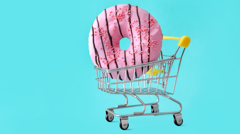 Shopping cart holding a donut against blue background