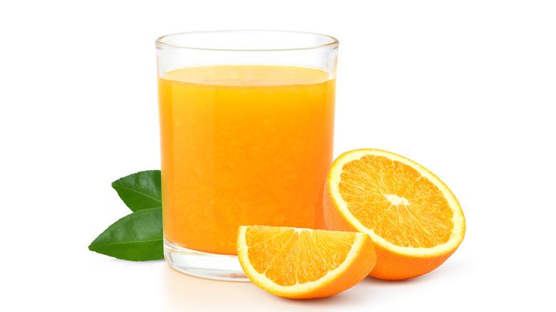Sliced orange next to glass of orange juice on white background