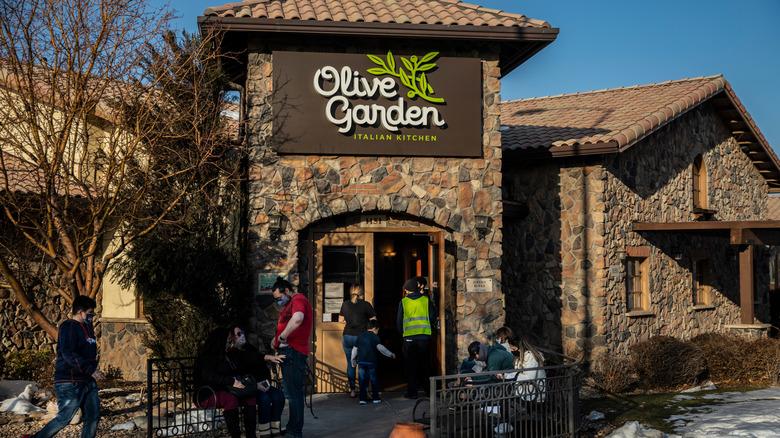 People walking outside Olive Garden restaurant