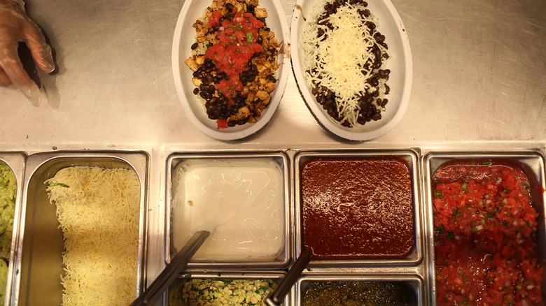 Chipotle bowls next to containers of salsa