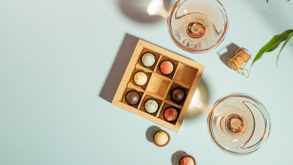 Glasses of wine with a box of colorful chocolates