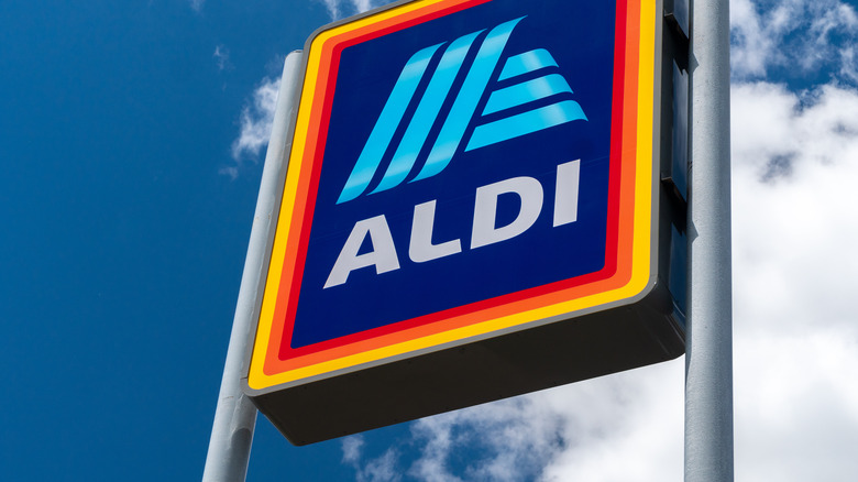 Aldi Store Sign against blue sky with clouds